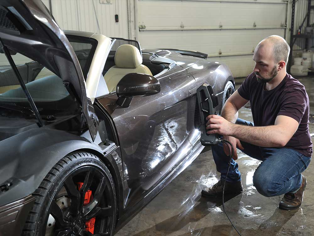 man holding go scan 3d device and scanning bmw car in automotive industry